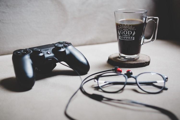 コーヒーとメガネが置かれたテーブルにゲームのコントローラーがある|Photo by Sabri Tuzcu (instagram.com/saber.shot)